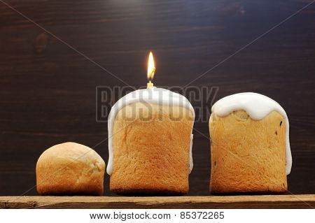 Kulichi, Traditional Russian Easter Cake With Icing And Candle On Wooden Background