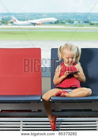 Child with phone in the hands the airport