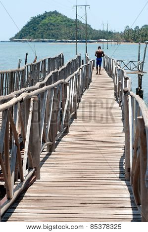 Man walking at traditional Wooden  Long Bridge Over The Sea,Thailand.