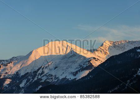 illuminated peaks of austrian mountain at winter evening