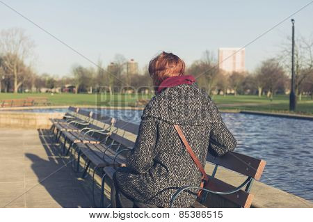 Woman Relaxing By Water In A Park