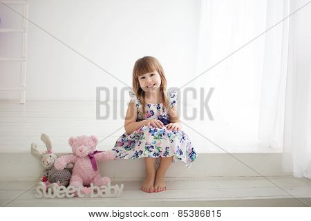 little girl sitting next to toys
