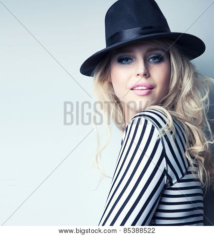 Young attractive blonde woman wearing hat and stripy top fashion concept
