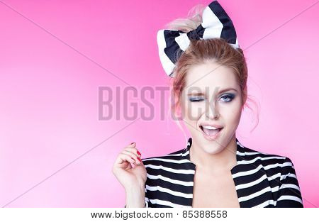 Excited winking young attractive woman on pink background