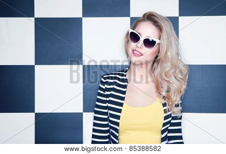 Attractive young woman wearing sunglasses on checkered background, beauty and fashion concept