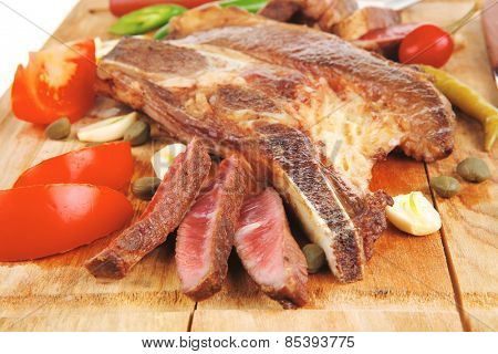 red meat steak sliced on wooden board with green hot pepper and cutlery isolated  over white background . shallow dof