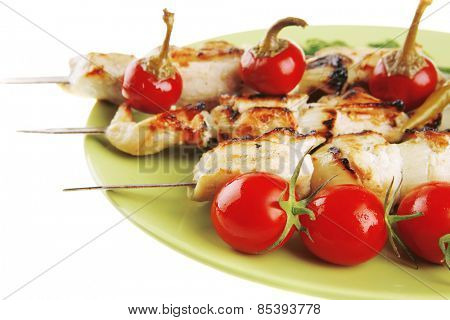fresh grilled  shish kebab on green platter with vegetables