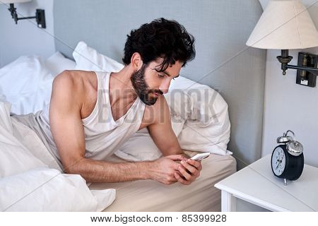 man with mobile cellphone laying in bed at home