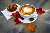 picture of glass heart  - A hot coffee latte with foam in the shape of a heart and a chocolate peanut better dessert sit on a glass table with some red and orange leaves during autumn - JPG
