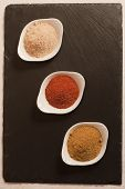 foto of garam masala  - different powder spices aligned on a slate plate  - JPG