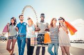 picture of overspending  - Group of friends holding shopping bags  - JPG