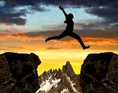 foto of country girl  - Silhouette the girl jumping over the gap at sunset - JPG