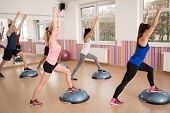 stock photo of fitness  - Group of young fit people exercising with bosu in fitness club - JPG