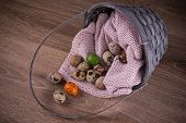 image of quail egg  - Quail eggs and one orange green egg spilling out of basket with pink textile - JPG