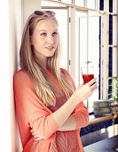 stock photo of daydreaming  - Young blonde woman drinking tomato juice - JPG