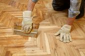picture of hand tools  - Varnishing of oak parquet floor workers hand and tool - JPG