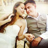 stock photo of couple sitting beach  - Romantic young couple sitting on the beach resting after wedding ceremony - JPG