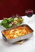 stock photo of lasagna  - baking dish with lasagna and salad on a table  - JPG