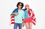 image of funky  - Funky young couple covering with American flag and smiling while standing against white background - JPG
