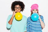 picture of funky  - Funky young couple inflating balloons while standing against white background - JPG