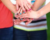 foto of joining hands  - People joining their hands  standing on green grass  - JPG