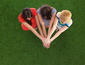 stock photo of joining hands  - People joining their hands  standing on green grass  - JPG