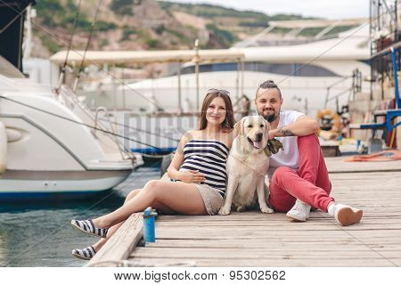 A young couple on a walk in the Harbor with a white Labrador