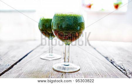 Green vegetable juice in wine glass