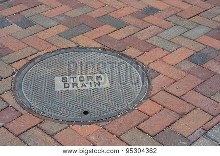 Storm Drain Cover On A Brick Road