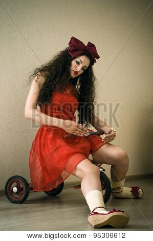 woman in a red dress on a bicycle in the form dolls