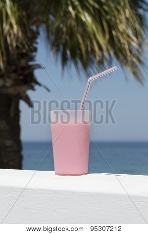 Pink Beverage In Plastic Cup Against Blue Sea And Sky