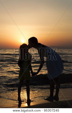 Mother And Daughter Kissing At Sunset On Seashore