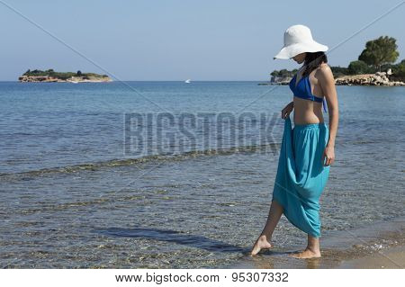 Woman Standing On A Beach And Looking Far Away