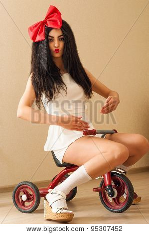fashionable beautiful woman in the image of doll on bicycle