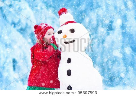 Funny little toddler girl in a red knitted Nordic hat and warm coat playing with a snow