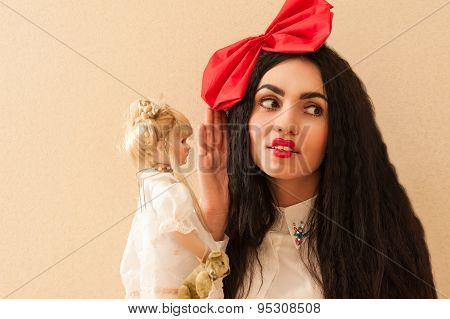 beautiful woman with a red bow surprised listening to gossip dolls