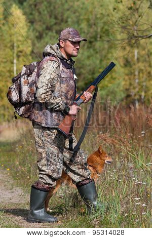 Hunter With A Dog In The Forest