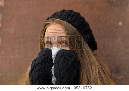 Sick Young Woman In Winter Attire Blowing Her Bose
