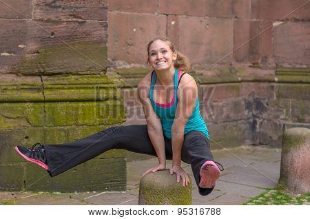 Athletic Woman Balancing Her Body On Bollard