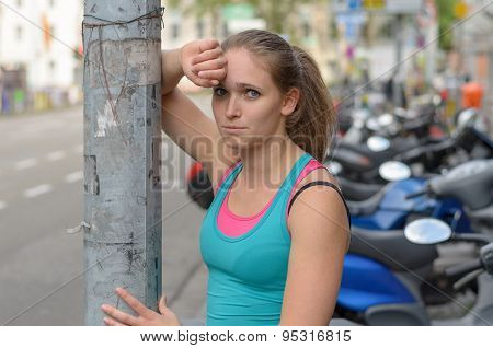 Athletic Girl Leaning Against The Street Post