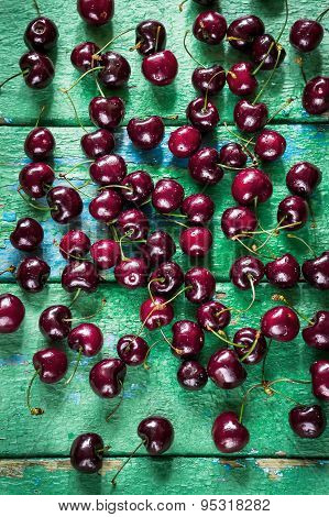 Cherry On  Green (turqouise) Wooden Background.