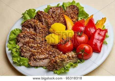Tenderloin steak wrapped in bacon with nut sauce with fresh herbs and olive oil