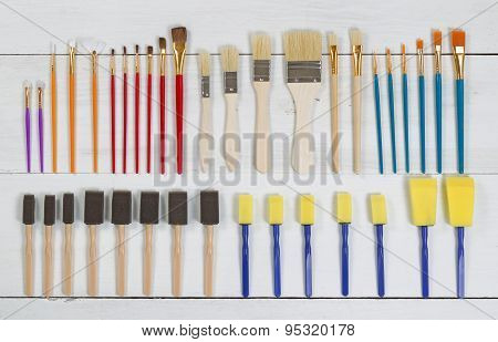 Organized New Paintbrushes And Applicators On White Wooden Boards