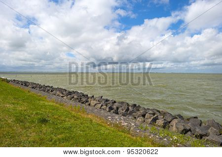 Basalt rocks protecting a dike along the coast of a sea