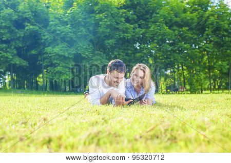 Happy Caucasian Couple In Love Lying On The Grass Outdoors. Reading Personal Ebook Reader