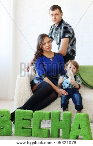 Mother, Father And Little Son Sit On White Couch In Light Room Near Text: Spring