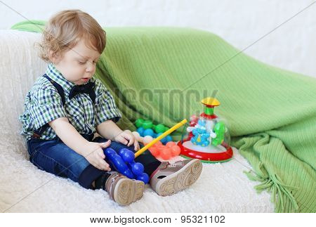 Little Handsome Happy Boy Sits On Soft White Sofa And Plays With Toys