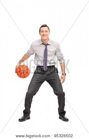 Full length portrait of a young businessman playing basketball and looking at the camera isolated on white background