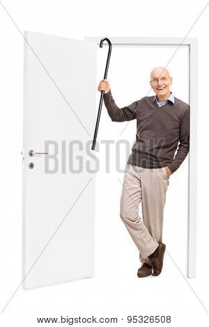 Full length portrait of a joyful senior showing his cane and leaning on the frame of an open door isolated on white background