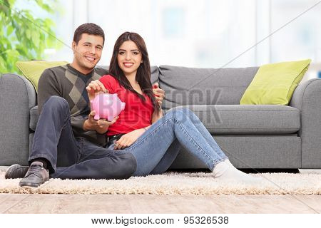 Young couple inserting a coin into a piggybank seated by a gray sofa at home
